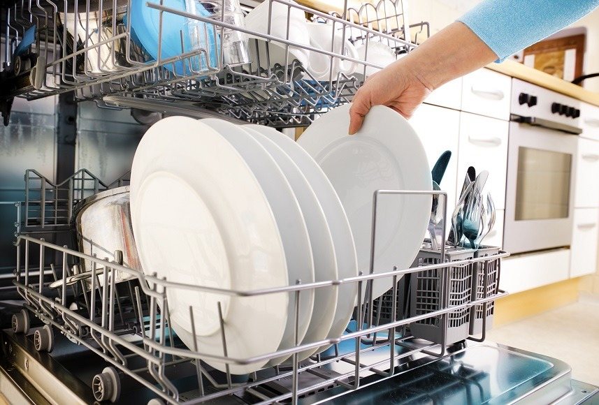 female hands loading dishes to the dishwasher