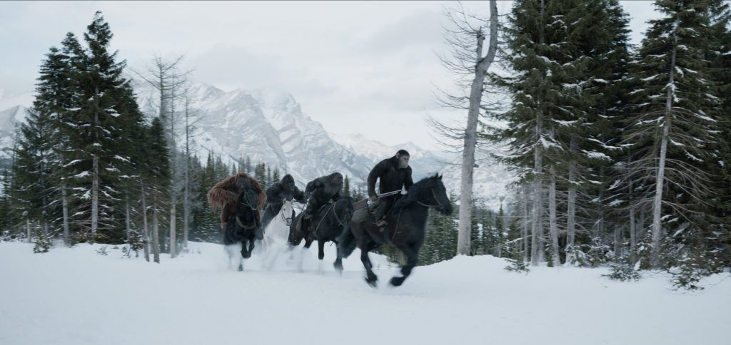 Men and apes riding horses through the snow