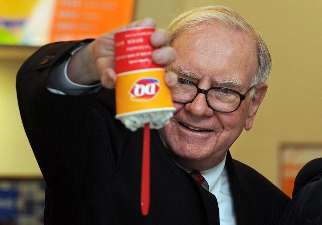 Warren Buffet holding a thick milkshake upside down.