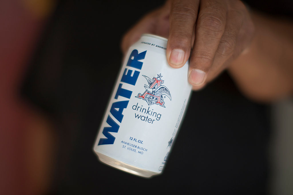 A resident holds a can of water donated by the Anheuser-Busch company in a drought-stricken area