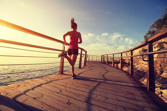 woman running on a wooden platform next to the sea.