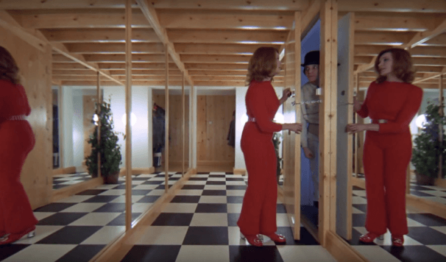 A woman in red opens a door in a mirrored hallway in A Clockwork Orange