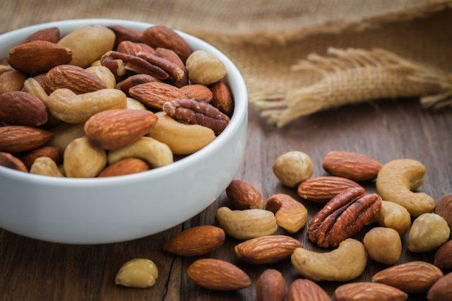 A white bowl full of healthy mixed nuts.