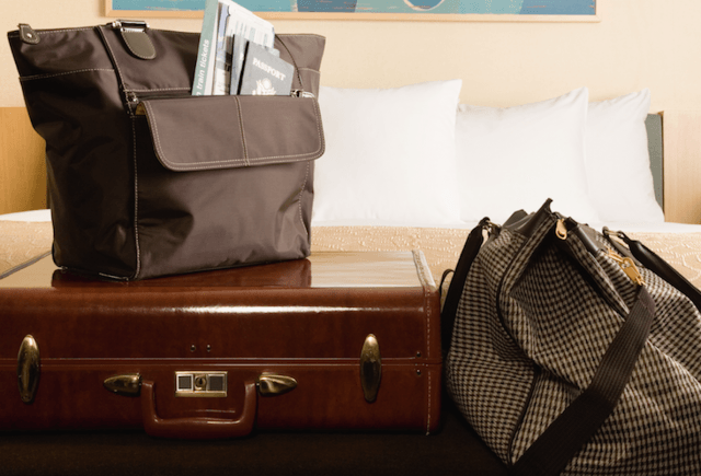A suitcase and carry-on bags in a hotel room.