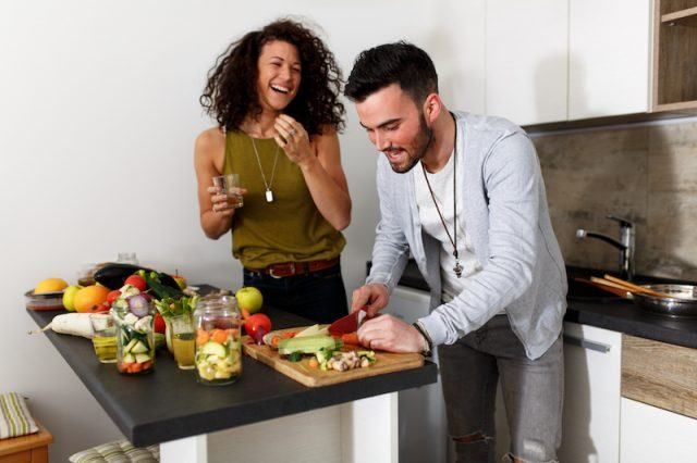A happy couple cooks a healthy meal at home.