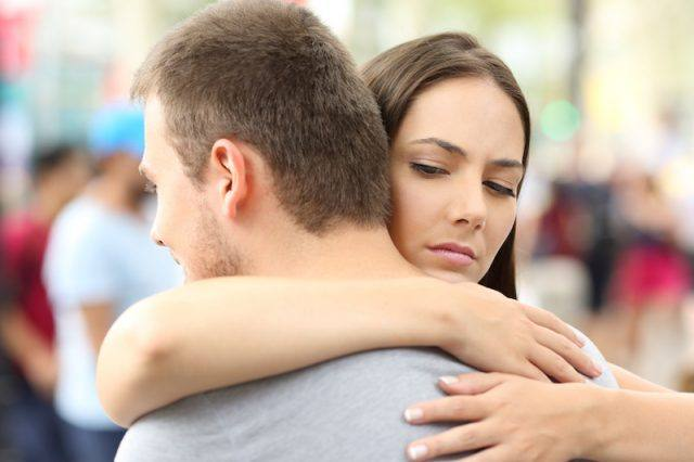 A discontent woman gives her partner a hug.