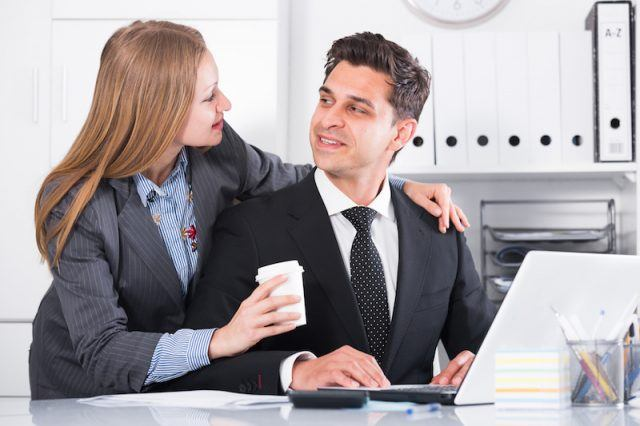 A man looks at his colleague as she puts her arm around his.