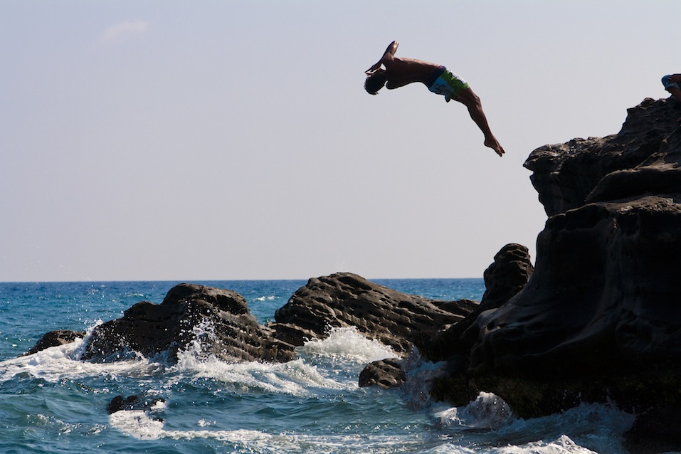 A man that is jumping from the rocks into the sea
