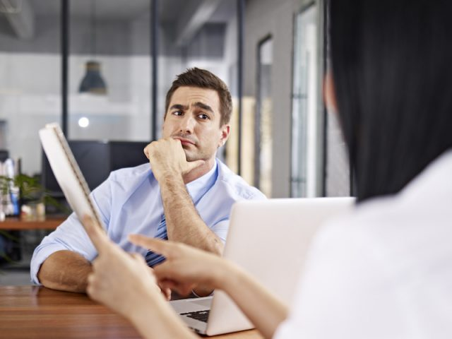 A man looks at a woman while they work.
