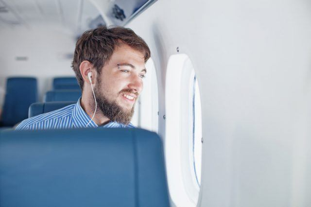 A man wears headphones while looking out the window.