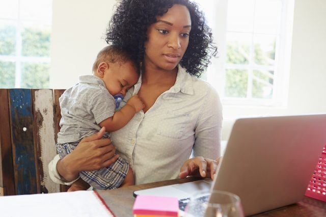 A woman and her baby sit in front of a computer.