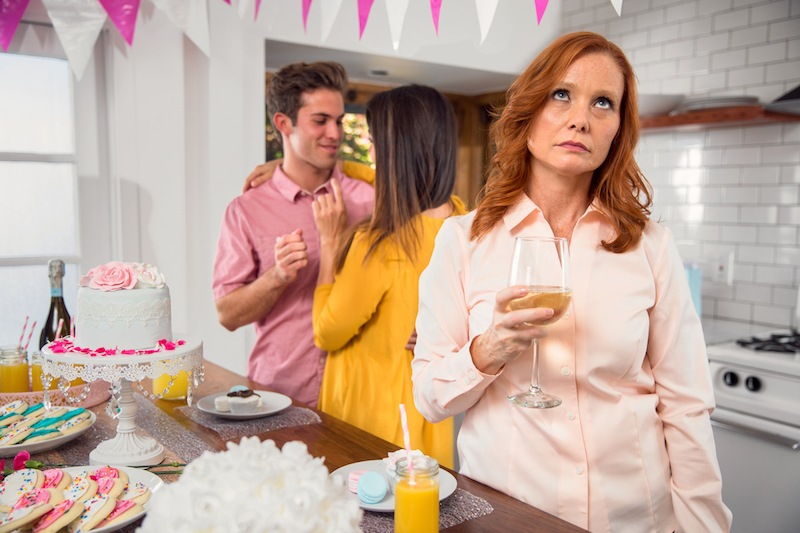 woman rolling eyes at couple at party