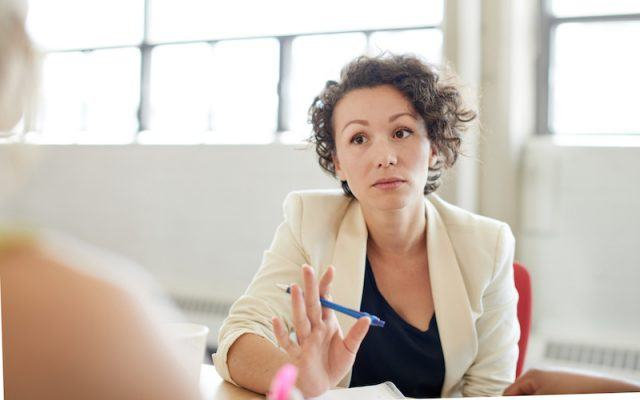A woman looks tense during a meeting.