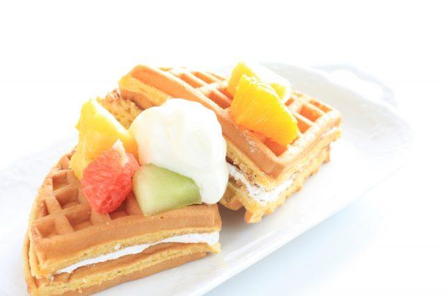 A waffle with fruit and yogurt on a white plate.