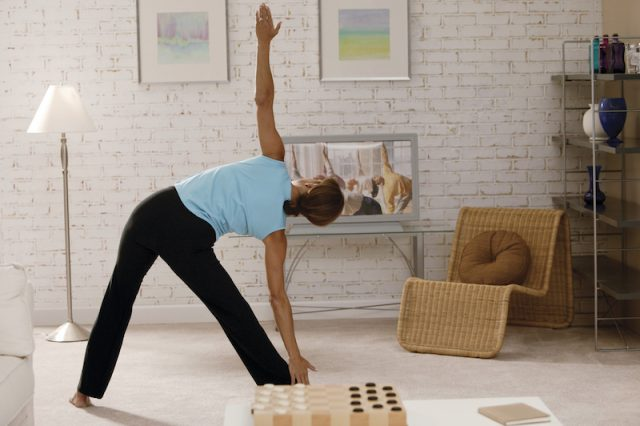 A woman does a workout in front of her television.