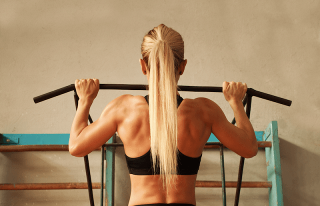 A woman does a pull-up at a gym.
