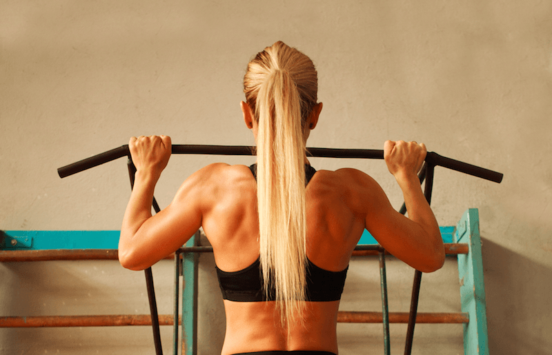 A woman doing pull-ups at a gym