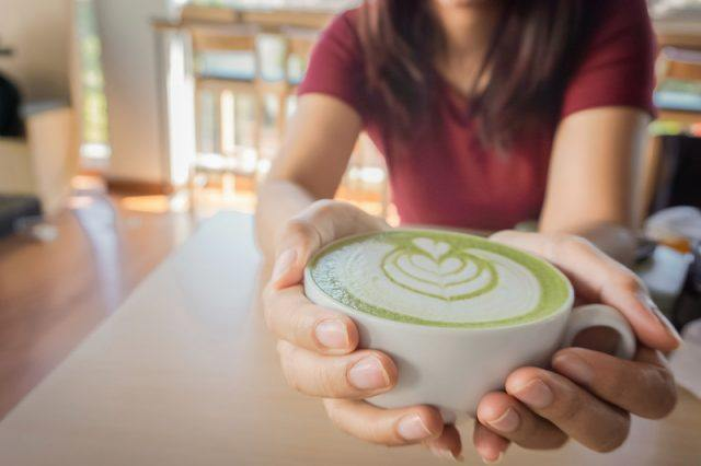 a woman holding a cup filled with matcha green tea