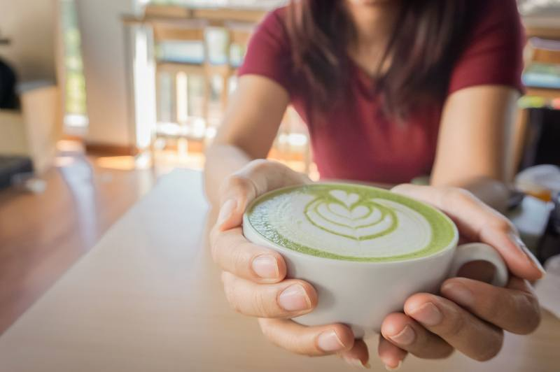 Woman holding a cup of hot matcha green tea in her hands