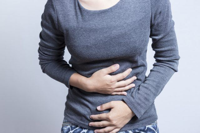 A woman holds her stomach with both hands.