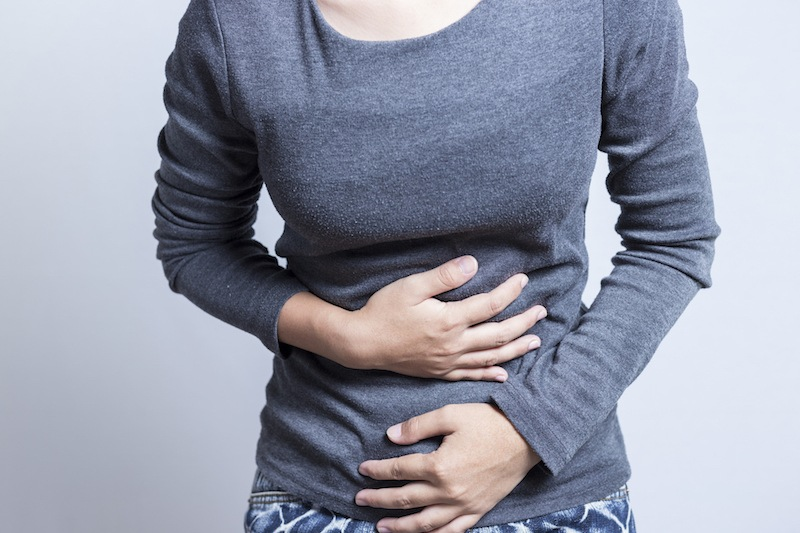 woman with a stomachache clutching her stomach