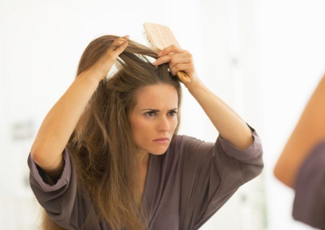 A woman inspects her hair in the mirror.