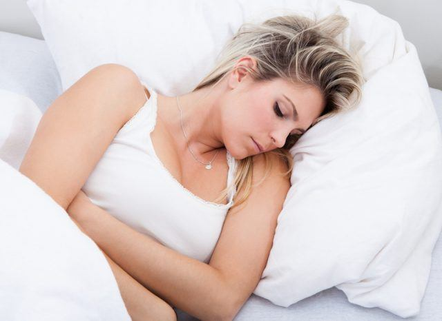 A woman lies in her bed holding her stomach.