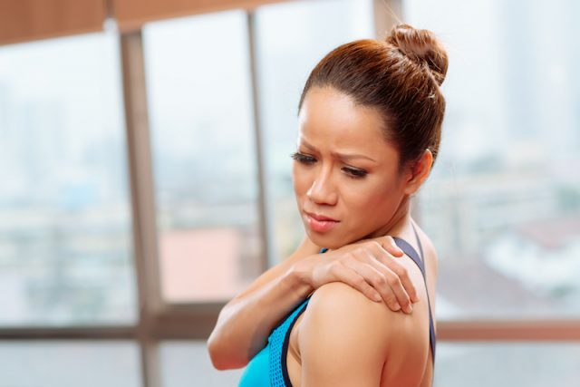 A woman rubs her sore muscle.