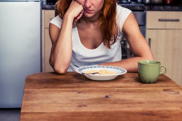 A woman sits at a table with a bowl of cereal in front of her.