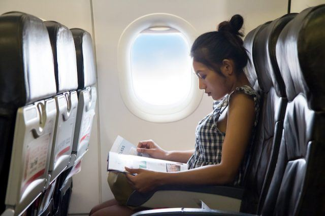 A woman sits in a window seat plane reading a magazine.