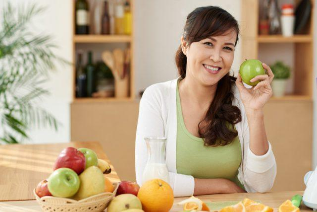 A woman sits with a basket of fruits on the table.