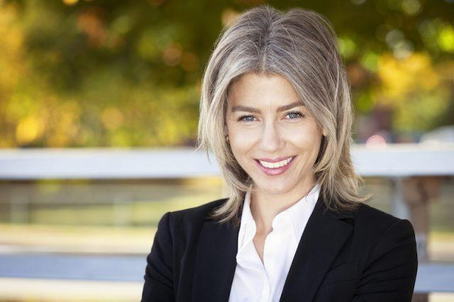 A woman with gray hair smiles in a suit.