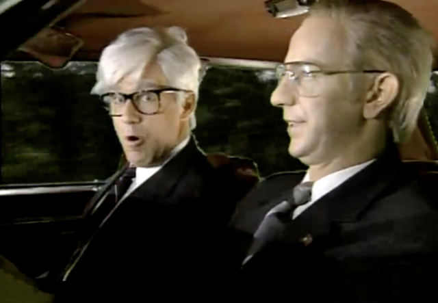 Two men sit in a car in suits