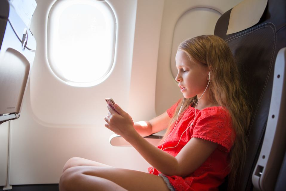 Adorable little girl traveling by an airplane