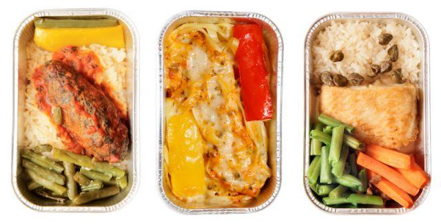 Airplane food in containers on a white background.