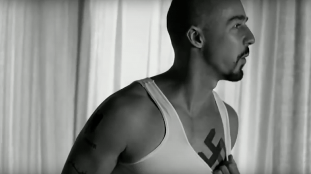 Derek pulls down a white shirt to reveal a swastika tattoo in American History X