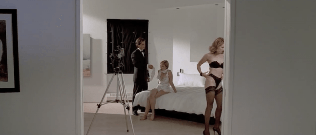 A man in a suit stands with in a room with two woman in lingerie