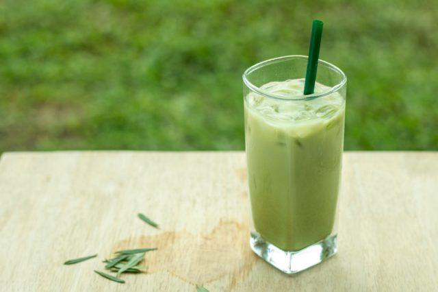 An iced matcha beverage being enjoyed outdoors.