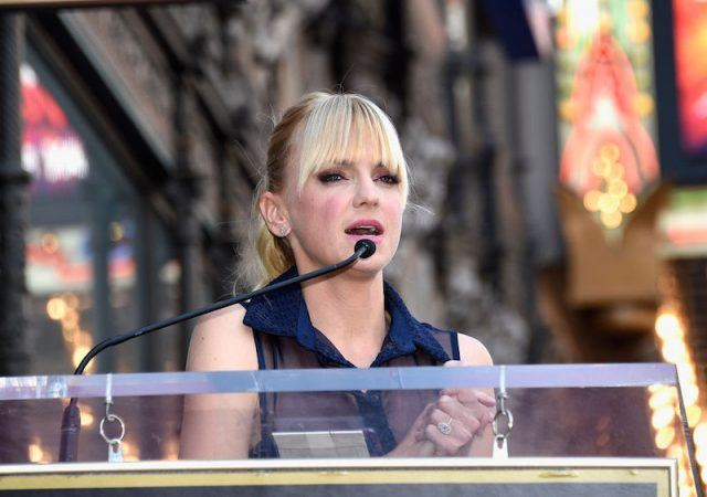 Anna Faris stands at a podium making a speech.