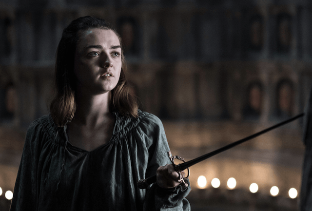Arya stands holding her sword.