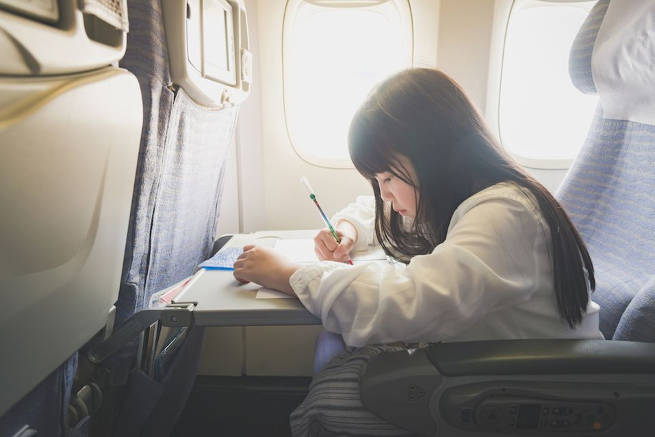 Asian girl painting with color pencil on airplane