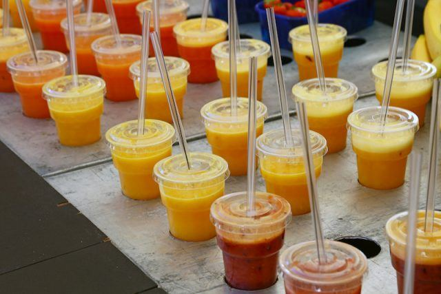 An assortment of yellow, red and orange smoothies on a table.