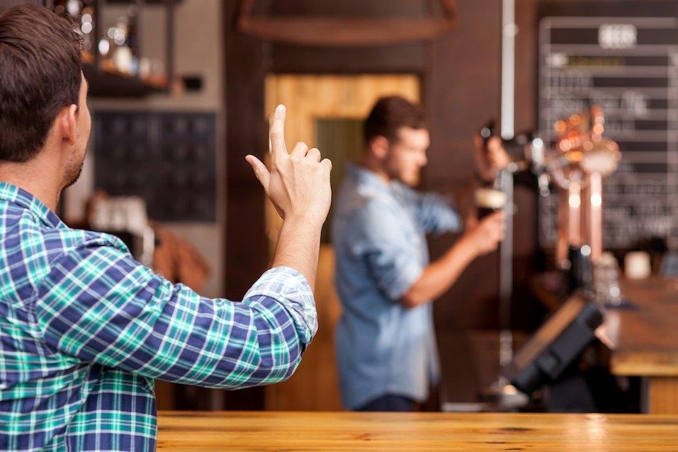 Cheerful man is ordering beer in bar