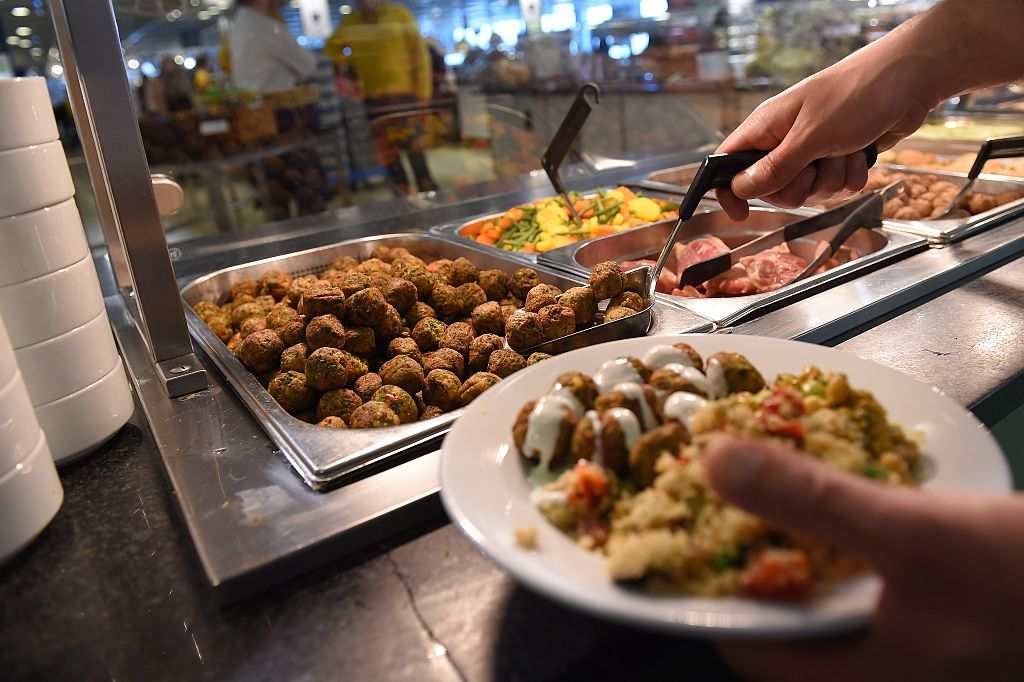 An IKEA employee serves the new IKEA vegetarian meatballs