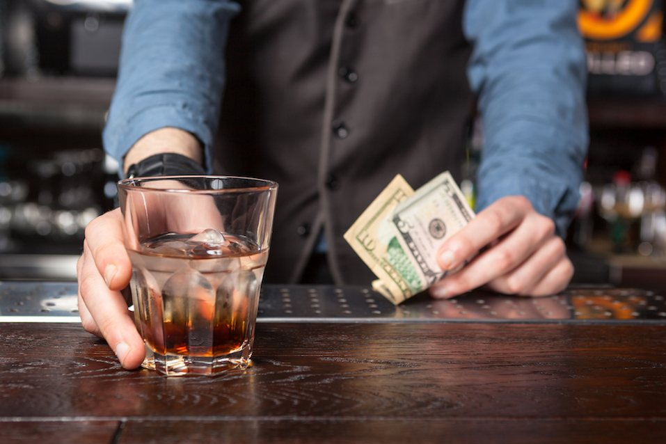 Barman giving whiskey glass with booze