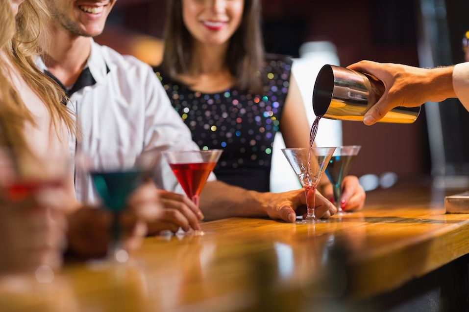 Bartender pouring cocktail for customers