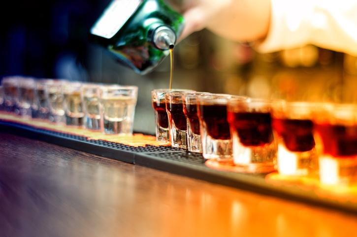 A bartender pours alcohol