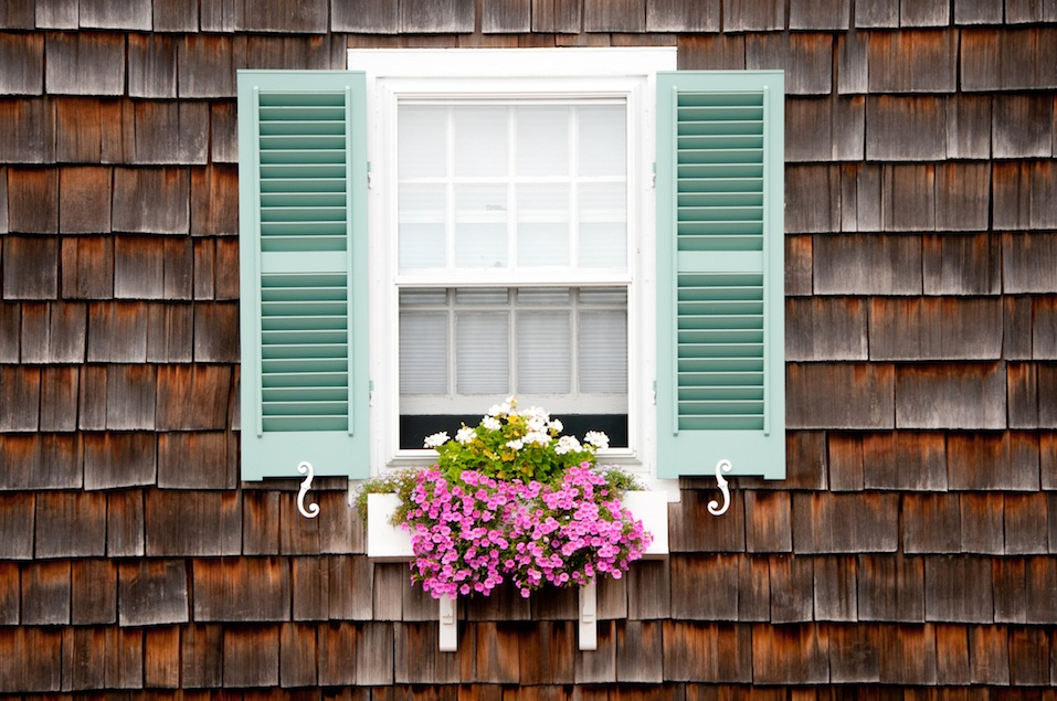 Window with turquoise shutters and white wooden window box and trailing pink and white flowers in summer