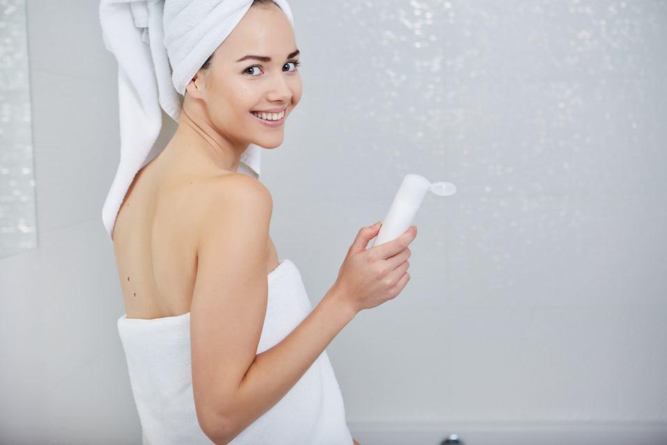 Beautiful Woman applying facial moisturizing cream
