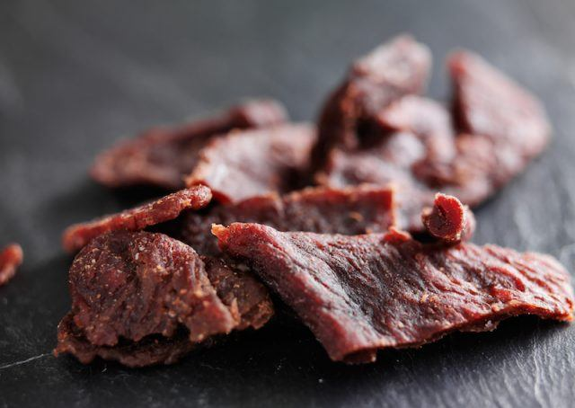 Pieces of cut dry beef on a wooden table.